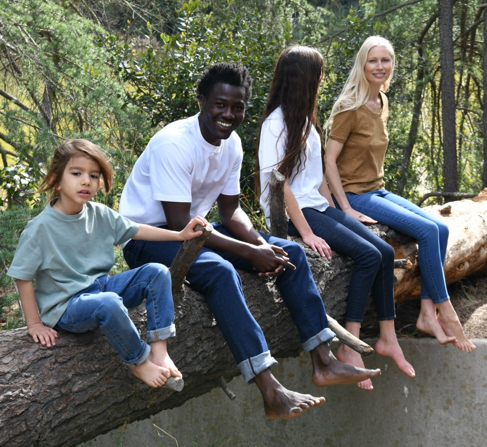 Group of young people wearing blue denim jeans sitting on a log in the woods